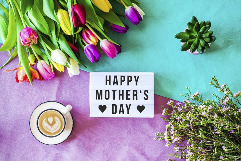 Shot from above as flatlay with happy mother's day message written on light box with coffee and colorful tulips and flowers